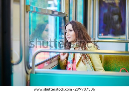 Beautiful young woman travelling in a train of Parisian subway and looking through the window