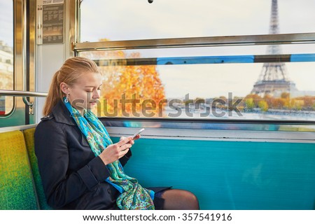 Beautiful young woman travelling in a train of Parisian underground and using her mobile phone. Eiffel tower is behind the window - stock photo