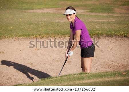 Beautiful young woman trying to get out of a sand trap in a golf game