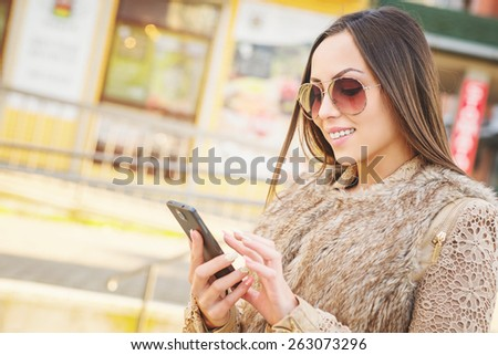 Beautiful young woman typing message/surfing on internet over smart phone outside. Shallow depth of field.