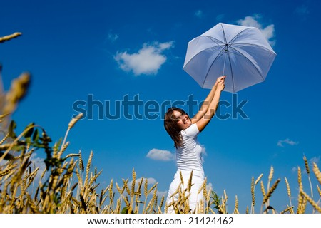 Beautiful young woman under blue sky with umbrella in the field. Smiling face