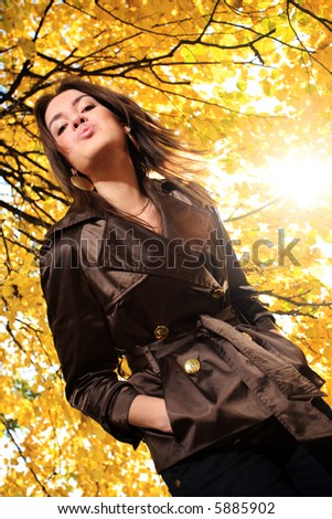 Beautiful young woman under tree branches with yellow autumn foliage in park, blowing a kiss. - stock photo