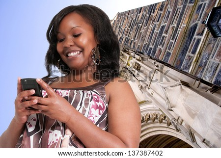 Beautiful young woman using a cell phone for texting - stock photo