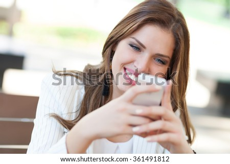 Beautiful young woman using a cellphone  - stock photo