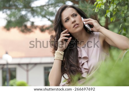Beautiful young woman using cell phone in park - stock photo