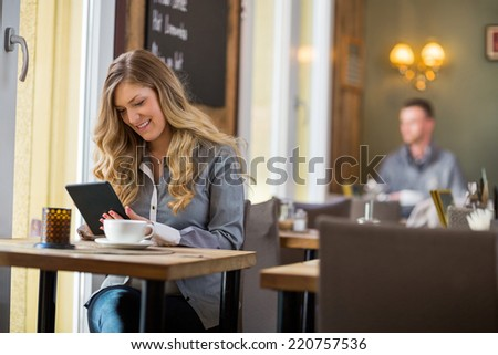 Beautiful young woman using digital tablet at table - stock photo