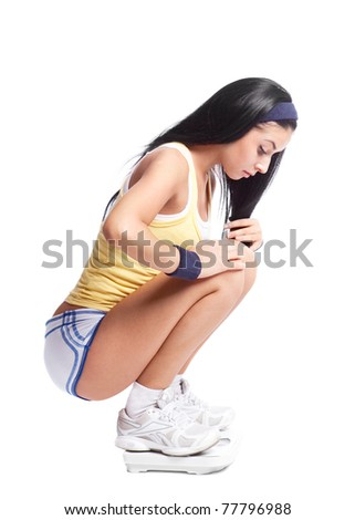 beautiful young woman using floor scales for measuring her weight, isolated against white background - stock photo