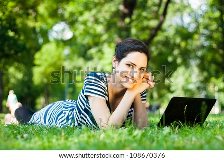 Beautiful young woman  using her laptop outdoors in a park/at campus - stock photo