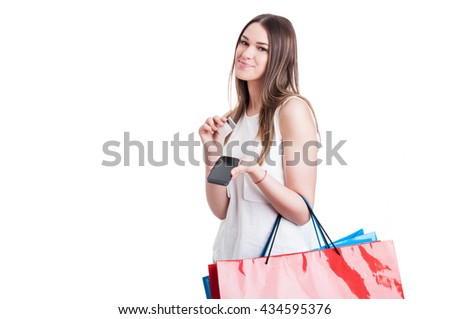 Beautiful young woman using her smartphone and credic card while doing some shopping as electronic payment concept isolated on white with copy space - stock photo