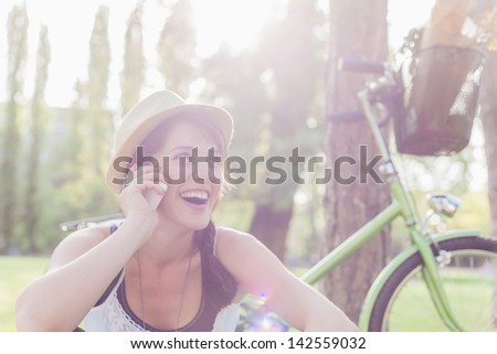 Beautiful young woman using mobile phone sitting next to her bike. - stock photo