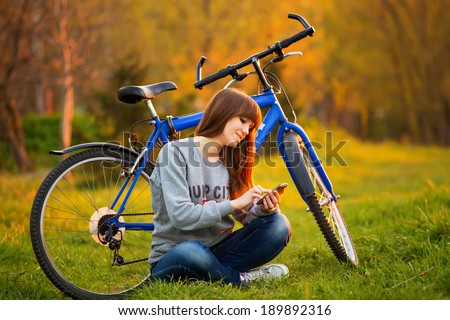 Beautiful young woman using mobile phone sitting next to her bike at sunset - stock photo