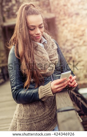 Beautiful young woman using mobile telephone on the fortress