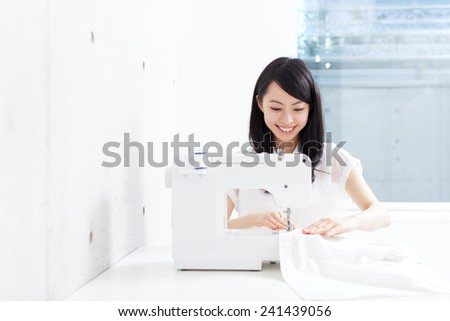 beautiful young woman using sewing machine - stock photo