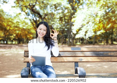 Beautiful young woman using tablet computer on a bench in autumn park  - stock photo
