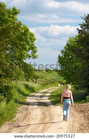 Beautiful young woman walking down country road - stock photo