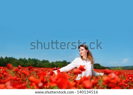 Beautiful young woman walking in a poppy field looking to the sky - stock photo