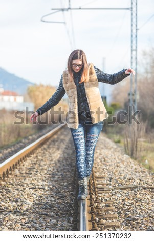 Beautiful Young Woman Walking in Balance on Railway Tracks. The Railroad is in a Residential Aerea. The Girl has a Casual Look. - stock photo