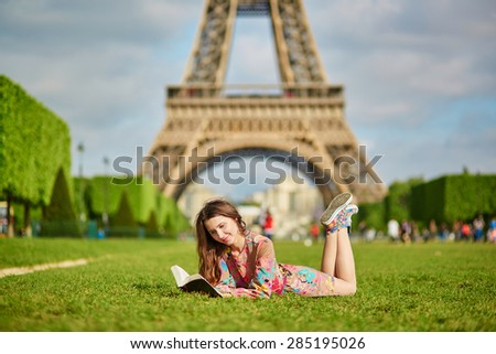 Beautiful young woman walking in Paris lying on the grass near the Eiffel tower on a nice spring or summer day and reading a book. Student or schoolgirl doing her homework or preparing to exams - stock photo