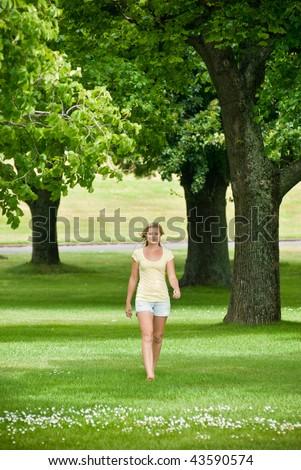 Beautiful young woman walking in park - stock photo