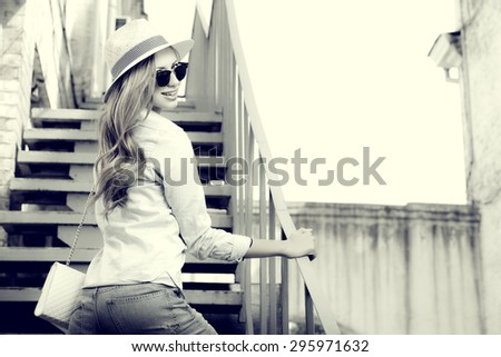 Beautiful young woman walking in the city. Fashion. Black-and-white photo. - stock photo