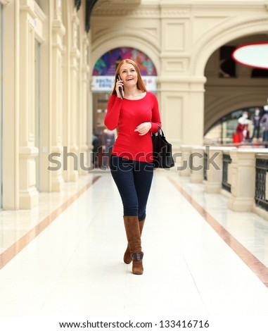 Beautiful young woman walking in the shop - stock photo