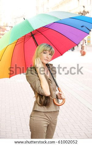 Beautiful young woman walking in the street with umbrella