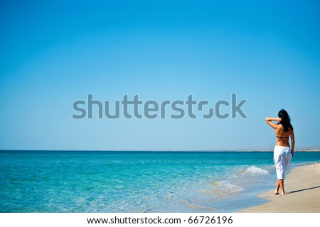 Beautiful young woman walking on the sand - stock photo