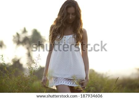 Beautiful young woman Walking Through A Field At Sunset - stock photo