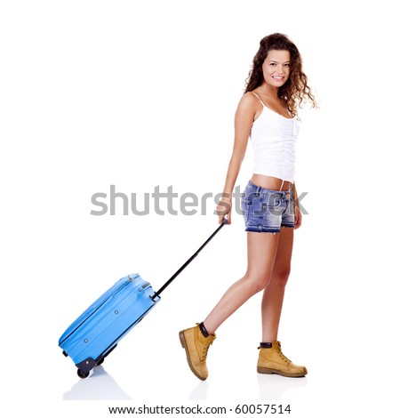 Beautiful young woman walking with a blue suitcase, isolated on white background - stock photo