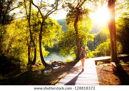 Beautiful young woman walks in Krka national park in Croatia at sunset - stock photo