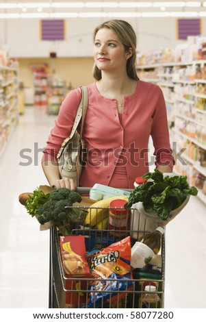 Beautiful young woman walks through a grocery store with a shopping cart full of food.  Vertical shot. - stock photo