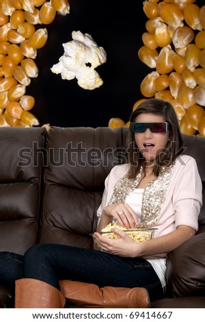 Beautiful young woman watching a 3d dvd movie on tv at home - stock photo