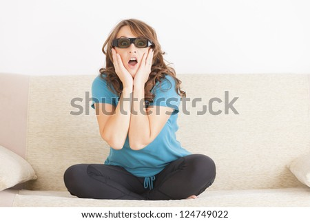 Beautiful young woman watching 3D TV in 3d glasses - stock photo