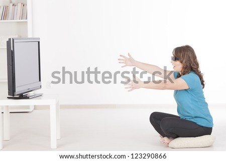 Beautiful young woman watching 3D TV in 3d glasses and trying to catch sometching