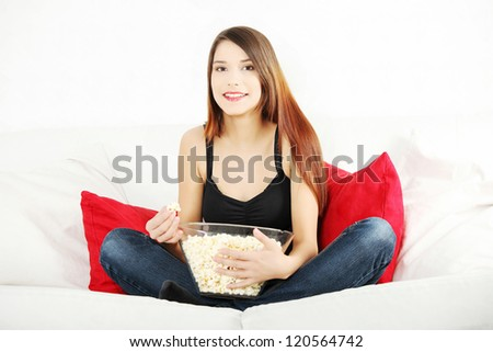 Beautiful young woman watching TV and eating popcorn - stock photo