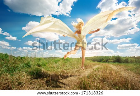 Beautiful young woman wearing a beige dress jumping on the grass - stock photo