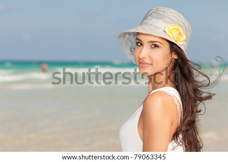 Beautiful young woman wearing a fancy hat and enjoying the pristine crystal clear shoreline of Miami's beautiful South Beach. - stock photo