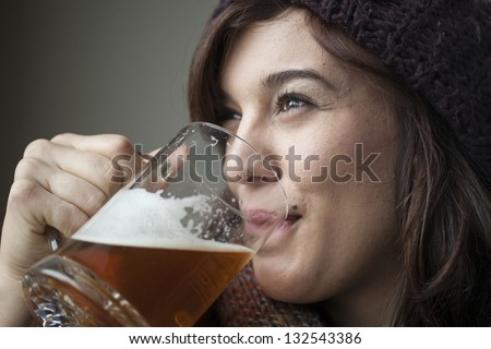 Beautiful young woman wearing a knit scarf and hat drinking a mug of beer. - stock photo
