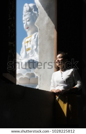 Beautiful young woman wearing a northern Thai dress at the back window of the Guanyin Bodhisattva, Huai Pla Kung Temple, Chiang Rai Province. Concept Travel Thailand.