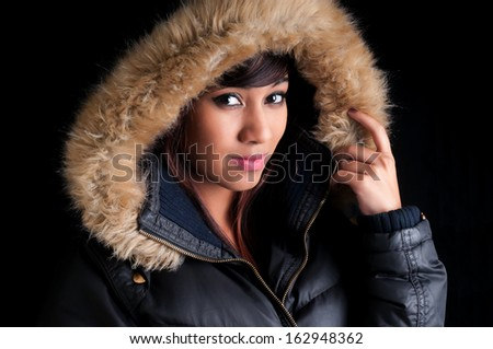 Beautiful young woman wearing a parka with imitation fur lining. - stock photo