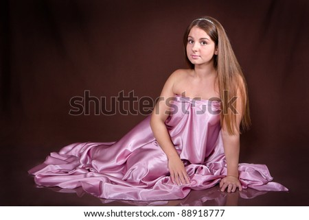 Beautiful young woman wearing a pink dress on dark background - stock photo