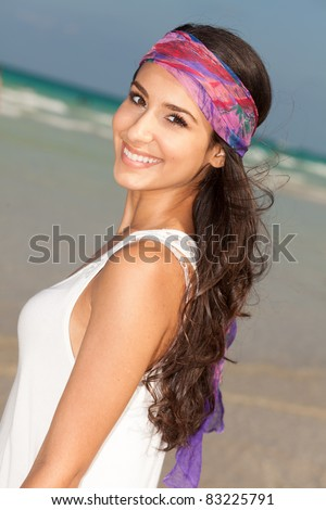 Beautiful young woman wearing a purple bandana enjoying the South Beach shoreline in Miami.