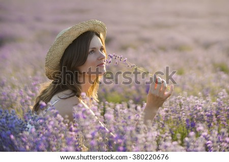 Beautiful young woman wearing a straw hat, holding a bunch of lavender flowers, enjoying their fragrance sitting in the middle of a lanvender field at sunset. - stock photo