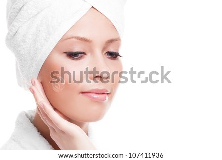 beautiful young woman wearing a towel and a white bathrobe applying cream on her face, isolated against white background, copyspace to the right - stock photo