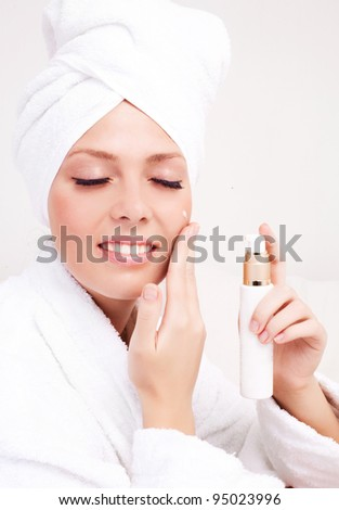 beautiful young woman wearing a towel and a white bathrobe applying cream onto her face at home - stock photo