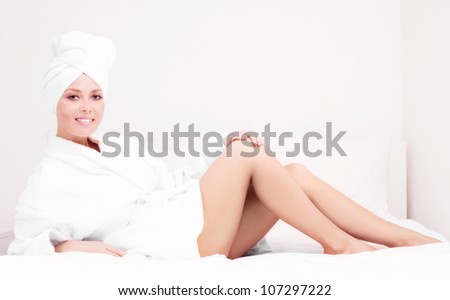 beautiful young woman wearing a towel and a white bathrobe in bed at home - stock photo