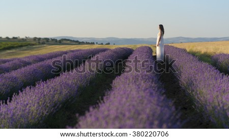 Beautiful young woman wearing a white dress standing in a middle of a lavender field in bloom looking in the distance. - stock photo