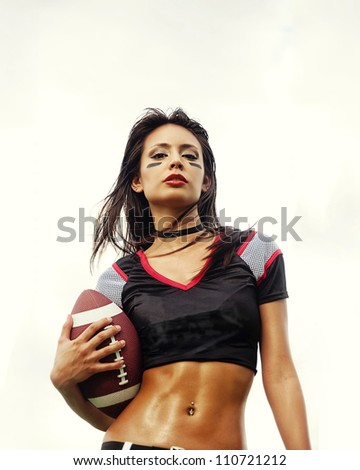 Beautiful young woman wearing American football top holding ball - stock photo