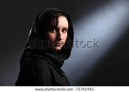 Beautiful young woman wearing black hijab looks quietly at the camera. - stock photo