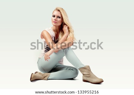 beautiful young woman wearing casual clothes and boots sitting on white background - stock photo